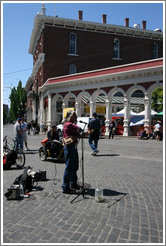 Street performer with one arm and two instruments.  Saturday Market.
