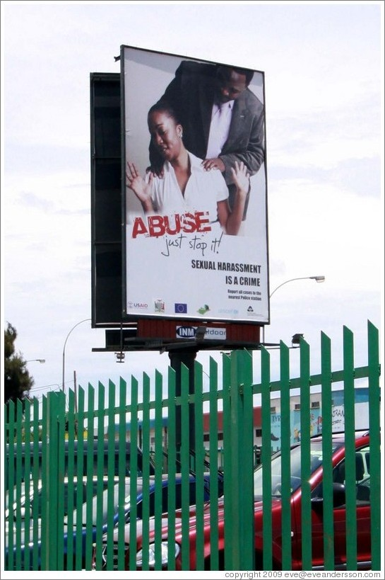"Billboard reading ""Abuse / just stop it / Sexual harassment is a crime""."
