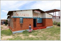 Makeni Viro Clinic, with a girl standing in front.  Garden District.